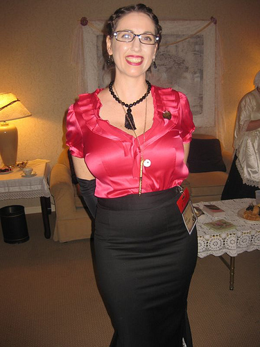 Gail Carriger, grinning, in a shiny pink shirt and black skirt