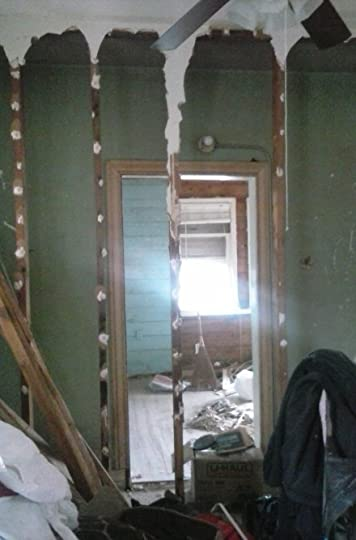Bedroom door revealed when makeshift closet is removed in dining area.