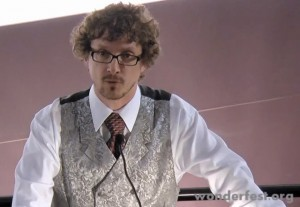 Photo of Richard Carrier in white shirt, red and grey striped tie, and silver vest, speaking at the podium of Wonderfest.