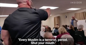 Screencap of video of the town hall mob, showing an angry man from the back jabbing his finger in the air at the poor guy assumed to be Muslim, merely an engineer presenting plans to the town hall for a new building, the transcript running below reports the man's words as Every Muslim is a terrorist, period. Shut your mouth.