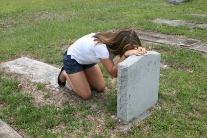 Young girl overcome with grief kneels in front of a loved one's grave.