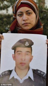 Anwar Tarawneh holds a photo of her husband Lt. Muath al-Kaseasbeh, before he was burned alive by ISIS.