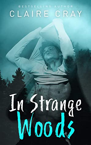 Book cover for IN STRANGE WOODS by Claire Cray. Superimposed over a foggy, dark blue-green treeline, a young man with his eyes closed and his head tilted back peels off a long-sleeved white shirt, exposing his torso.