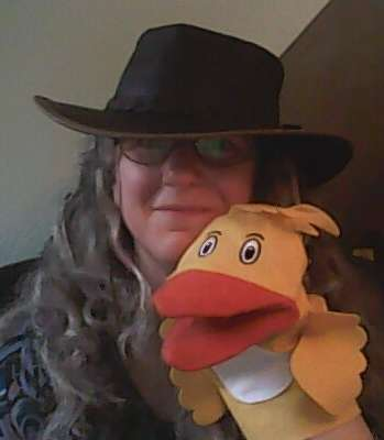 image of author wearing a hat and holding a duck hand puppet