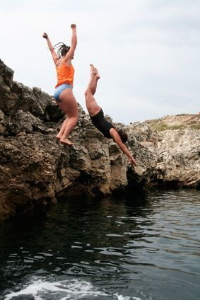 two people cliff diving: