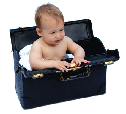 Picture Of Baby In A Somewhat Large Black Leather Hand Bag With Handles To It