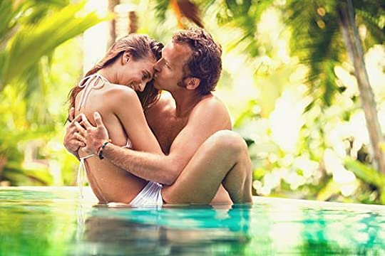 Loving couple kissing in tropical pool during summer.: