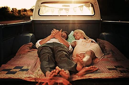 couple laying in the back of a truck