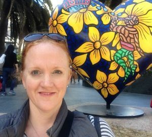 A picture of the author in front of one of the Hearts in San Francisco sculptures - a large navy blue heart with vivid yellow flowers