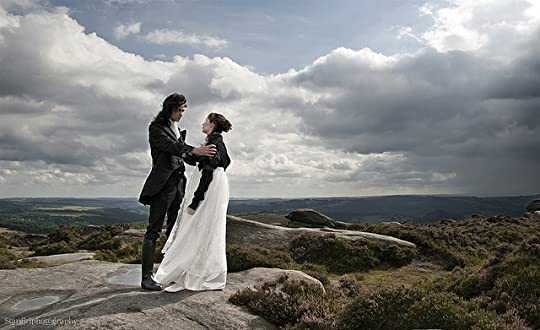 2 white people standing on a rocky outcropping overlooking the moors, each dressed in costume suggesting they are representing Catherine and Heathcliffe from Wuthering Heights