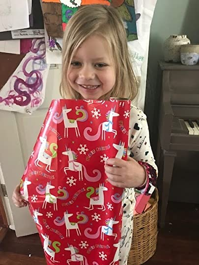 Poppy holding unicorn wrapping paper