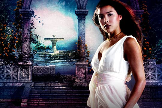 A picture of Maricela (tall, brunette, latina, dressed in a white dress) in front of a fountain behind two stone arches in the center of a garden maze.