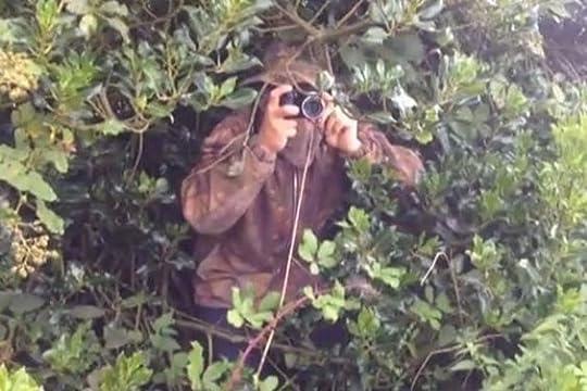 man hiding with camera