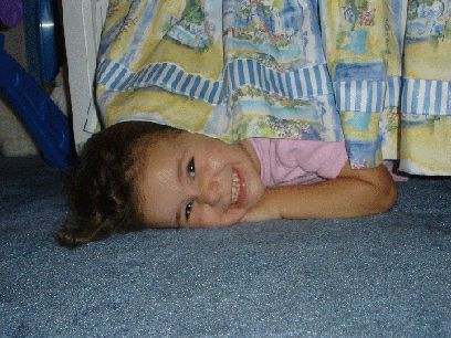 little girl hiding under the bed