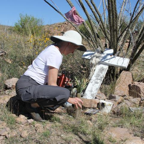 Woman placing something at a desert gravesite