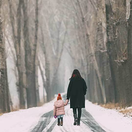 Mother and daughter alone on snowy road