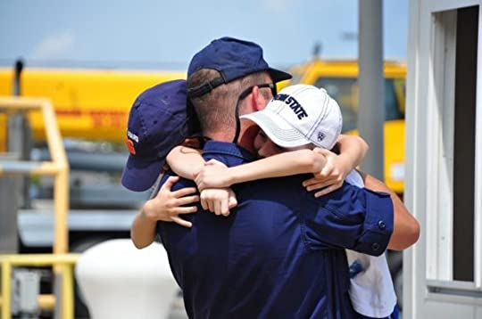 Military dad hugging his two kids with a semi-truck in the background.