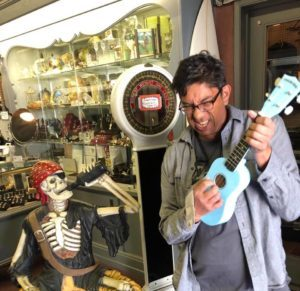 Greg with a blue ukulele and a pirate replica skeleton drinking booze