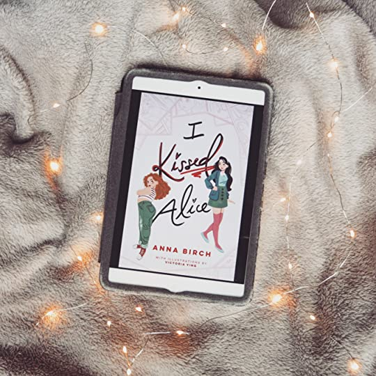 my bookstagram picture of the book in ipad with a grey blanket in the background