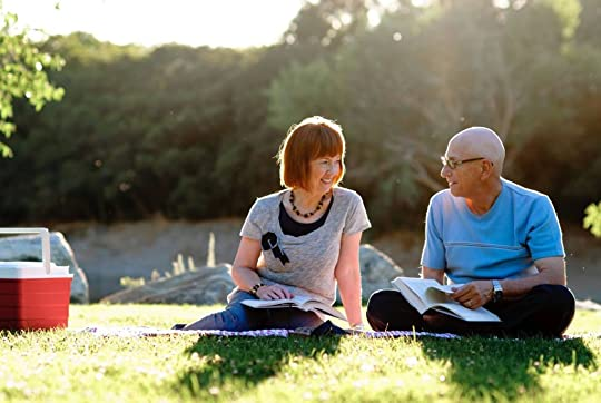 man and woman reading together on picnic blanket