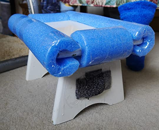 A white foot stool with blue foam taped around its edges.