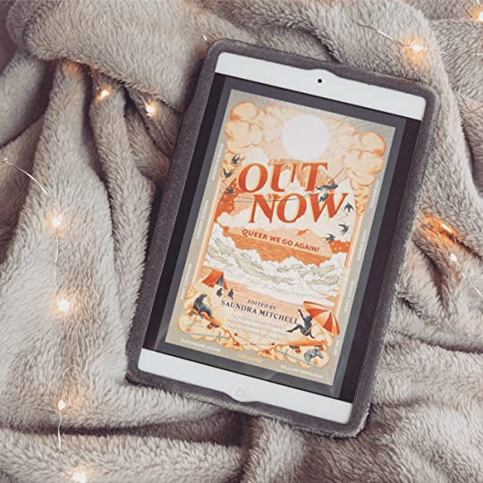 the cover of out now on an ipad on top of a grey blanket with fairy lights around it