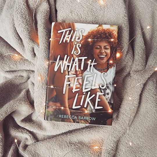 hardcover copy of this is what it feels like on a grey blanket with fairy lights