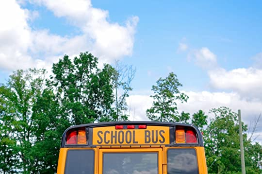 the back of a school bus against the backdrop of green leafy trees and a blue sky with wispy white clouds.