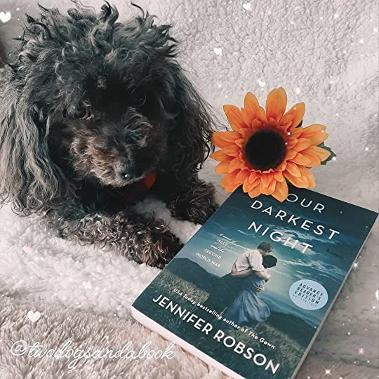 A cute dog with a copy of the book entitled Our Darkest Night by Jennifer Robson