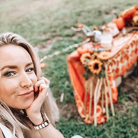 Blond woman with her chin on her hand, in the background in a beautiful green lawn and an altar draped with an orange cloth, cut sunflowers, candles, and pumpkins. She looks relaxed and joyful.