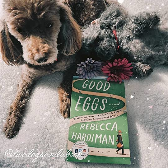 Two cutes dogs with a copy of the book entitled Good Eggs by Rebecca Hardiman