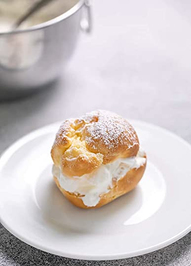 One cream-filled choux pastry on small white plate with confectioners sugar on top