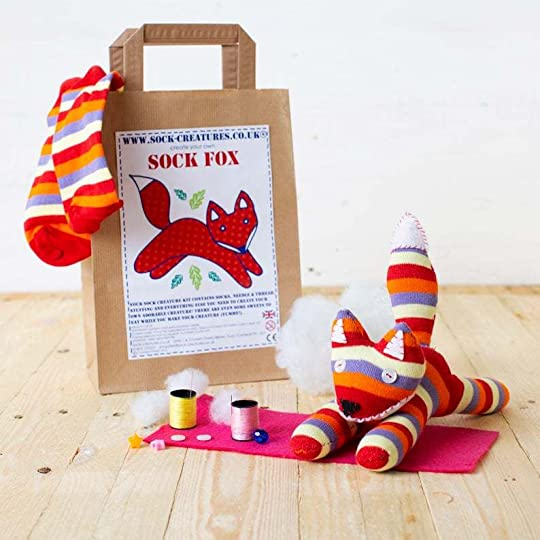 A Sock Fox craft kit - a paper bag with a picture of a jaunty fox, and a striped stuffed animal in front of it.