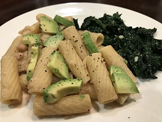 Rigatoni pasta mixed with white bean sauce and topped with sliced avocado and black pepper, with a side of braised kale
