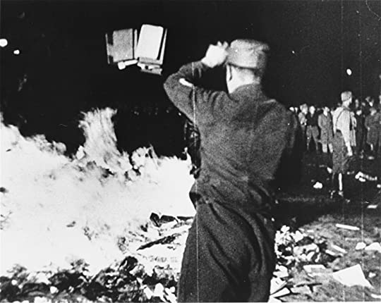 A member of the SA throws confiscated books into the bonfire during the public burning of